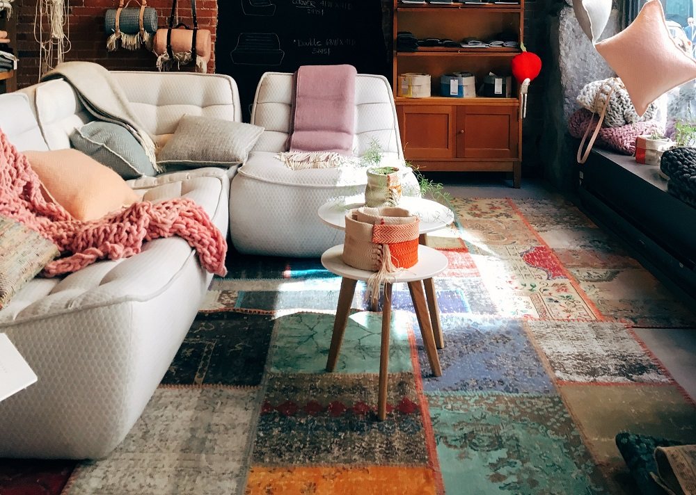 Cozy decor for the she shed with a couch, pillows, and carpet