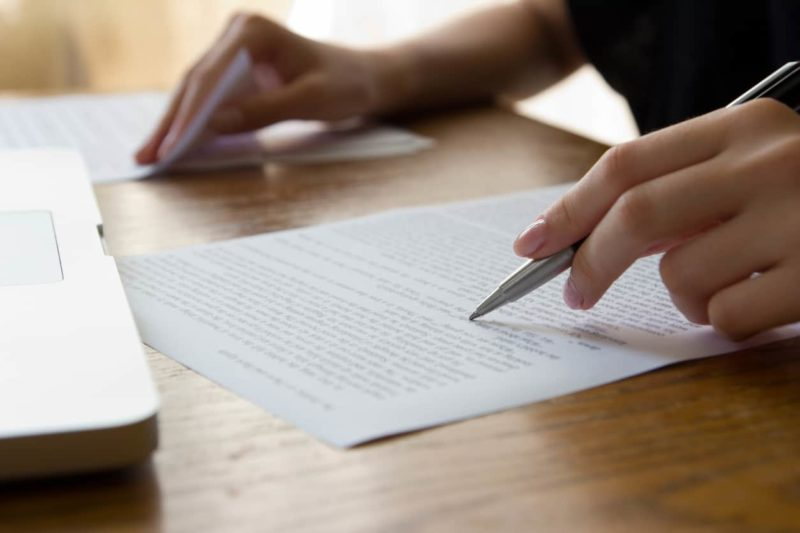 Hand holding a pen and writing a real estate offer letter