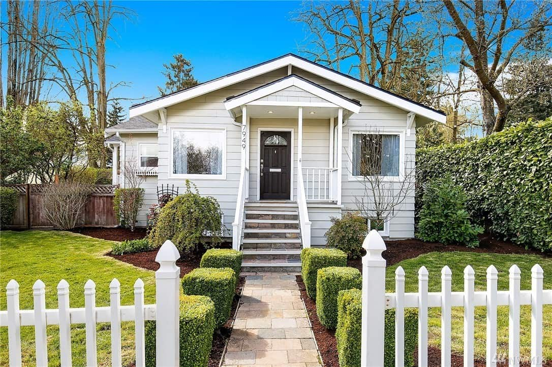 White craftsman home with white picket fence and shrubbery