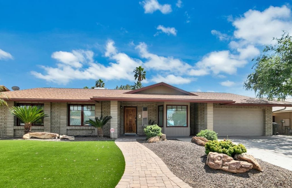 One story ranch-style home with grass yard and blue sky