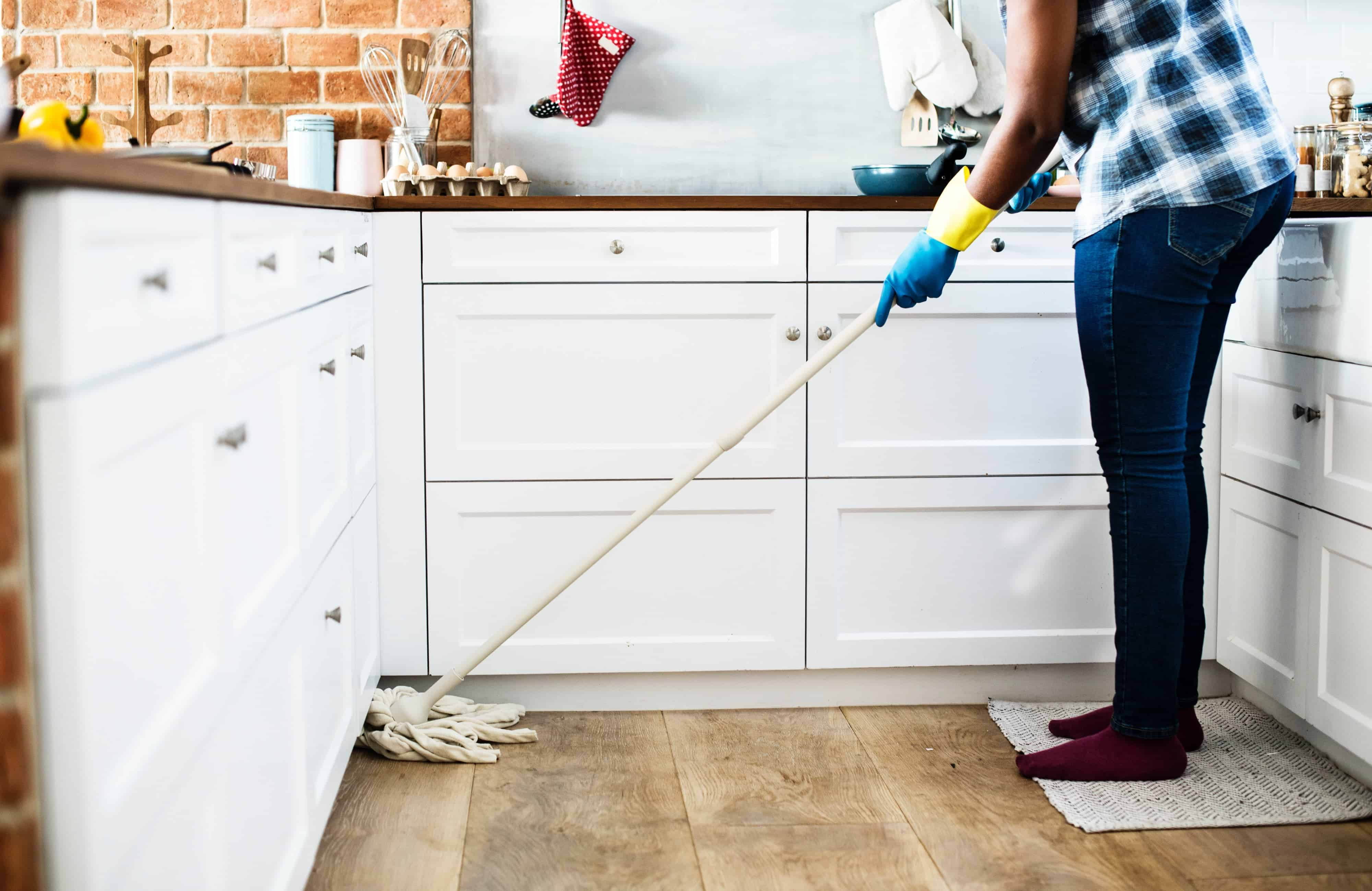person mopping hardwood floor