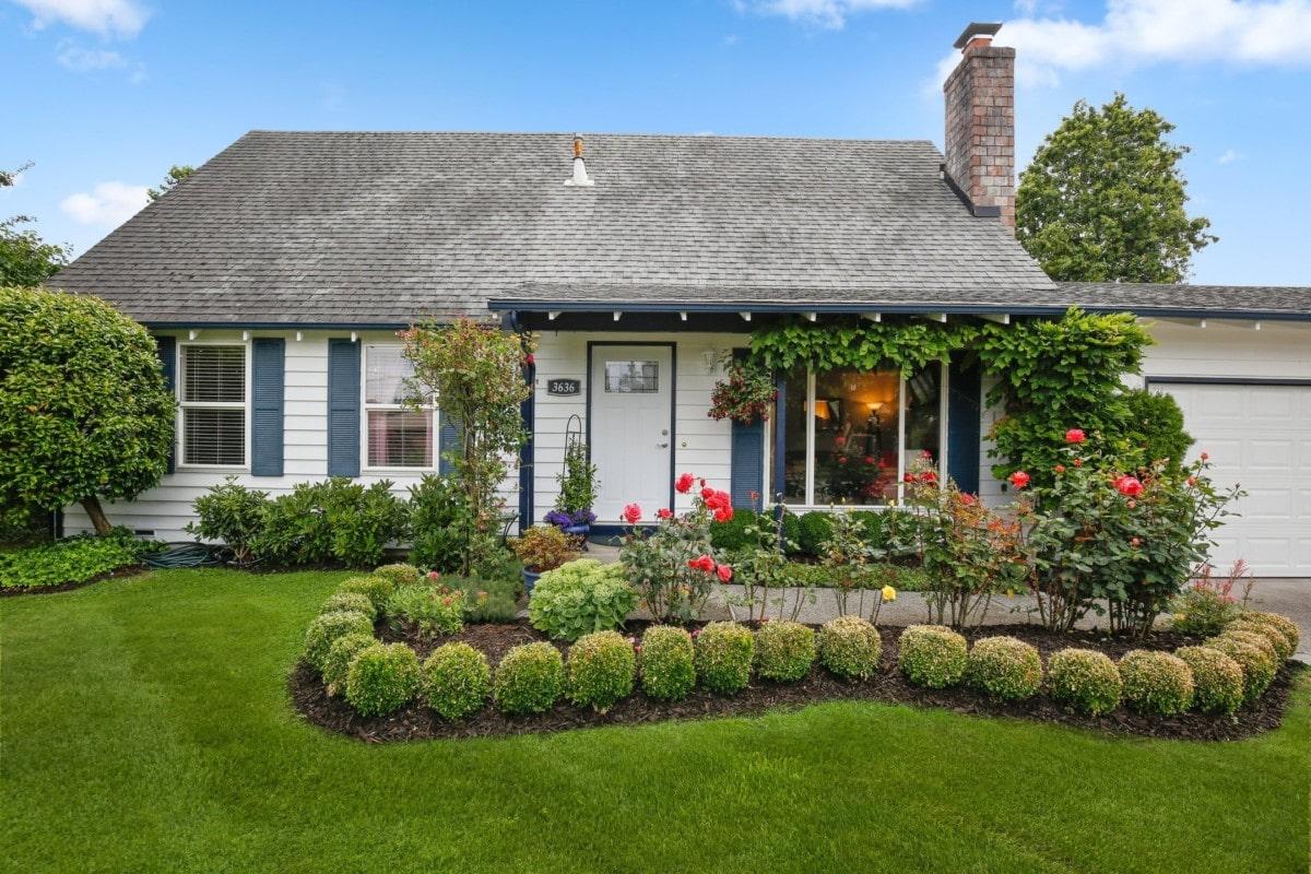 blue-house-front-porch-landscaped-yard